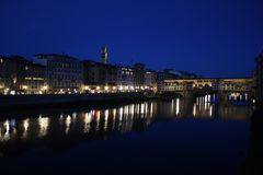 Famous bridge Ponte Vecchio with reflection in river Arno at night in Florence, Italy stock photography
