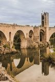 This is the famous bridge and tower of the medieval town of Besalú, in Girona, Spain. We can see the reflection on the water and stock photos
