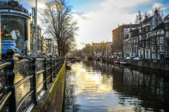 Famous buildings and place of Amsterdam city centre at sun set time. General landscape view. AMSTERDAM, NETHERLANDS - DECEMBER 28, 2016: Famous buildings and Stock Photos