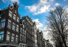 Famous buildings and place of Amsterdam city centre at sun set time. General landscape view. AMSTERDAM, NETHERLANDS - DECEMBER 28, 2016: Famous buildings and Stock Photography