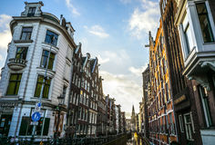 Famous buildings and place of Amsterdam city centre at sun set time. General landscape view. AMSTERDAM, NETHERLANDS - DECEMBER 28, 2016: Famous buildings and Royalty Free Stock Photo