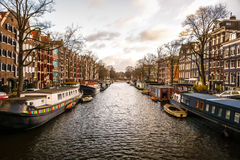 Famous buildings and place of Amsterdam city centre at sun set time. General landscape view. Royalty Free Stock Photo