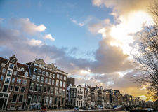 Famous buildings and place of Amsterdam city centre at sun set time. General landscape view. Royalty Free Stock Photos