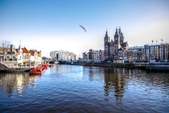 Famous buildings and place of Amsterdam city centre at sun set time. General landscape view. Royalty Free Stock Images