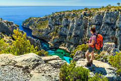 Famous Calanques D'En Vau in Cassis near Marseille,France. Young hiker woman with backpack and photo camera on the high cliffs,Calanques D'En Vau bay,Calanques Stock Photography
