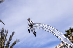 Famous Carnival of Nice, Flowers` battle. Clouds on clear blue sky  with an acrobat in businessman suit Royalty Free Stock Image