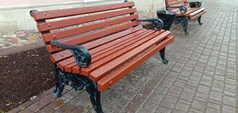 The famous, cast iron, cast with wooden backs Vladimir benches. For public use in public places. Russia stock image