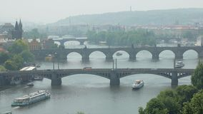 Famous Charles bridge in Prague and other bridges over Vltava river, city life with tourists stock footage