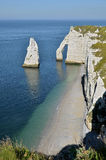 Famous cliffs of Etretat in France. Cliffs of Etretat with the famous pointed Aiguille (Needle) and the natural arche the Porte d'Aval. Etretat is a commune in Stock Photos