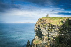 Famous cliffs of moher, castle tower, west coast of ireland. At wild atlantic ocean Royalty Free Stock Photography