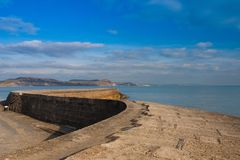 The famous cobb in Lyme Regis, England. The Cobb an old stone pier forming an extensive harbour and believed to date from the time of Edward I royalty free stock photography