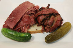 Famous Corned Beef and Pastrami on rye sandwich served with pickles Stock Images