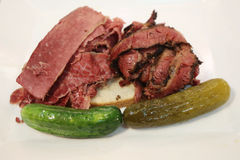 Famous Corned Beef and Pastrami on rye sandwich served with pickles Royalty Free Stock Photos