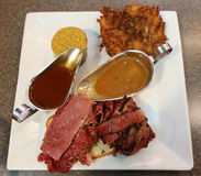 Famous Corned Beef and Pastrami on rye sandwich served with potato latke and kishka. In New York Deli Stock Photography