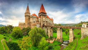 The famous corvin castle with cloudy sky,Hunedoara,Transylvania,Romania. Beautiful panorama of the Corvin castle with wooden bridge and small cascades,Hunedoara royalty free stock photography