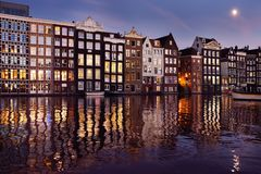 Famous dancing houses of the Damrak canal in Amsterdam at night stock photography