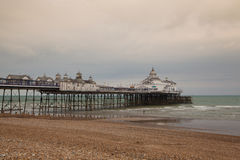Famous Eastbourne Pier and beach in cloudy day. Royalty Free Stock Images