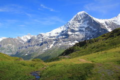 The famous Eiger with hiking path. Amazing view at the Eiger and hiking path from Maennlichen to Grindelwald in Switzerland. Mountain landscape Stock Photography