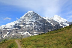 The famous Eiger north face with hiking path. View at the Eiger and Moench and hiking path from Maennlichen to Grindelwald in Switzerland. Mountain landscape royalty free stock images