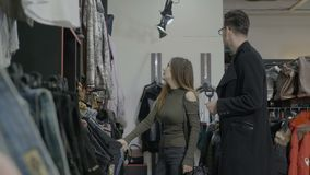 Famous female star walking in a clothing store with her stylist to choose the perfect outfit -. Famous female star walking in a clothing store with her stylist stock video