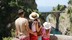 Famous fiordo di furore beach seen from bridge. Beautiful family enjoy the amazing view of Fiordo di Furore. Cala di Furore beach, bridge over the gorge Fiordo stock footage