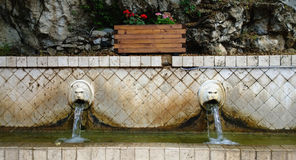 The famous fountain with the flowing water from the lions ` mouths in the village of Spili in Crete. Greece Royalty Free Stock Photo