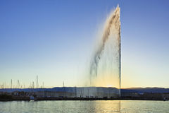"Famous fountain ""Jet d`Eau"" in Lake Geneva at sunset. Stock Image"