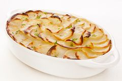 Boulangere or Scalloped Potatoes. Famous French dish of potatoes and onions baked with stock, Boulangere Potatoes, so called because in the past French Royalty Free Stock Photos
