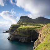 Famous Gasadalur waterfall from viewpoint during a sunny summer day with mountain peaks and calm sea. Amazing cliffs on the Faroe