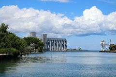 Famous Grain Elevators in Owen Sound, Ontario. View of the grain bins look at the mouth of the Owen Sound Harbour on a sunny summer day with fluffy white clouds royalty free stock images