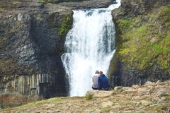 Hikers on the famous Haifoss waterfall in southern Iceland. Famous Haifoss waterfall in southern Iceland. treking in Iceland. ecouple hikers sitting on the edge Royalty Free Stock Images