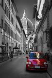 Famous historic red car in Florence street. Color in black and white. Old charming auto concept. Red small car is parked in narrow street of Florence with view stock image