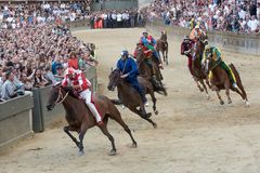 The famous horse race `Palio di Siena`. SIENA, ITALY - AUGUST 16, 2018: Riders compete in the horse race `Palio di Siena` in the medieval square `Piazza del stock images