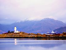 Famous Isle Ornsay with  Lighthouse tower, Isle of Skye, Scotland, UK. Snowy mountains in background Royalty Free Stock Images