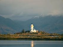 Famous Isle Ornsay with  Lighthouse tower, Isle of Skye, Scotland, UK. Snowy mountains in background Stock Photography