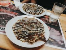The famous Japanese food in Osaka, named Okonomiyaki. the Japanese style fried pancake on wooden plate topping with vegetables, stock photos