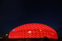 Red Allianz Arena. Famous landmark, exterior of the Allianz Arena in Munich, Germany. Night shot, the arena lit with red light, night sky as space for text, copy royalty free stock photography