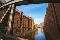Famous landmark old Speicherstadt in Hamburg, build with red bricks. Bridge in low angle view royalty free stock image