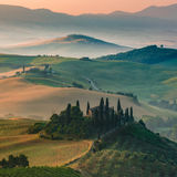 Famous landscape of Tuscany in hazy morning and sunrise. Famous hazy Tuscany farmhouse on the hill, Italy Royalty Free Stock Image