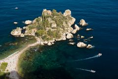 Little peninsula, Isola Bella, people at the beach, small boats around, blue sea in Taormina, Sicily, Italy. Famous little isle in east Sicily sea shore. Sunset stock photos