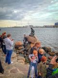 Famous Little Mermaid statue in Copenhagen. Surrounded by the tourist. Denmark stock photo