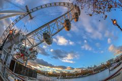 Famous London Eye at sunset. LONDON, ENGLAND - NOVEMBER 28, 2017: Famous London Eye and street lamp at sunset time. Giant Ferris wheel on the Bank of the River Stock Photo