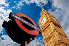 Famous London underground sign and Westminster Parliament on blu. E sky with clouds Royalty Free Stock Images
