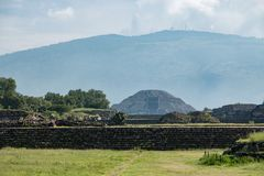 Famous and majestuous Mexican archaeological site. Sun pyramid during Mexico`s rainy season, green grass and flowers Stock Images