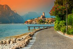 Fantastic Malcesine tourist resort and colorful sunset, Garda lake, Italy. Famous Malcesine touristic recreation resort, paved walkway with colorful flowers and royalty free stock photography