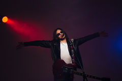 Famous male singer standing on stage with guitar and microphone Royalty Free Stock Images