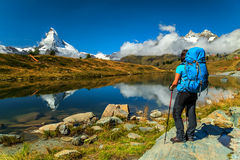 Famous Matterhorn peak and Leisee alpine glacier lake,Valais,Switzerland. Hiker woman with backpack looking at view in Valais region,Leisee lake,Switzerland Royalty Free Stock Photography