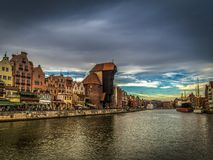 Famous medieval crane in the Gdansk , Poland in the evening with scenic dark blue cloudy sky stock photos