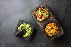 Famous mexican sauces salsas - pico de gallo, avocado guacamole, salsa bandera mexicana in stone mortars on gray slate background.  stock photo