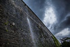 Ancient city wall spitting out when it rains stock photography